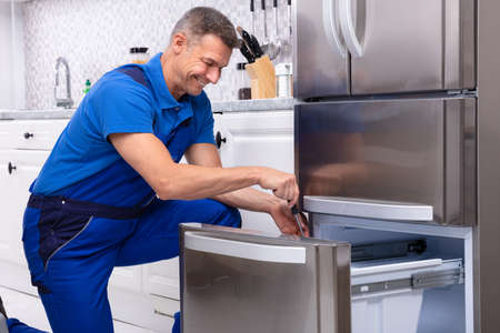 Mature Male Serviceman Repairing Refrigerator With Toolbox In  Kitchen 版權商用圖片