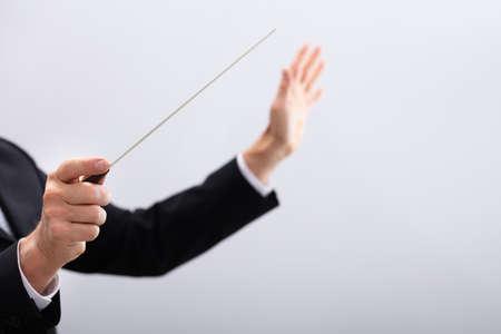 Nahaufnahme eines Musikdirigenten Hände halten Taktstock vor grauem Hintergrund