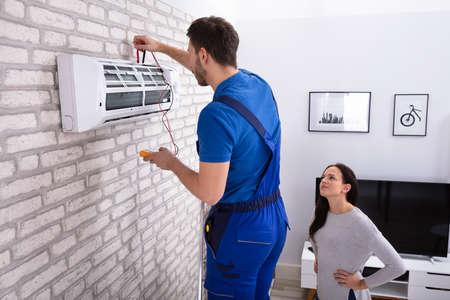 Donna sorridente che guarda il tecnico maschio che ripara il condizionatore d'aria con il multimetro digitale a casa Archivio Fotografico