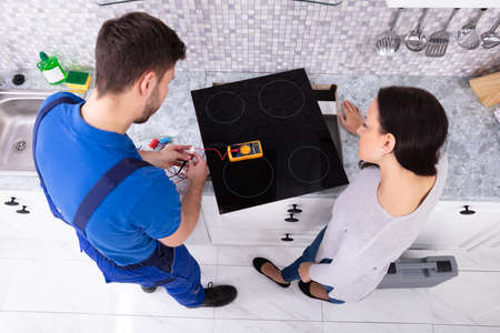 Male Repairman Installing Induction Cooker With Woman Standing In Kitchen Banque d'images