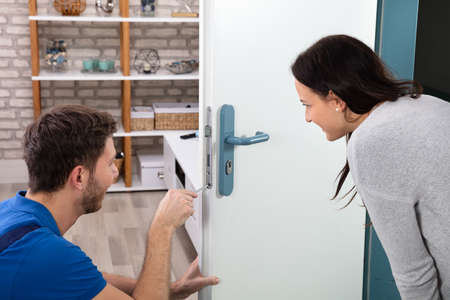 Smiling Woman Looking At Technician Fixing The Door Lock With Screwdriver At Home