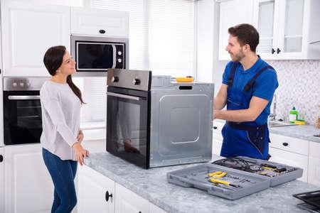 Réparateur souriant réparant le four sur le plan de travail de la cuisine en face de la femme