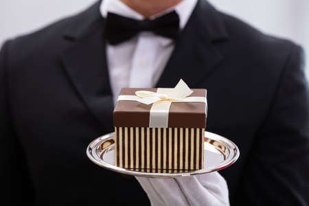 Close-up Of Male Waiter Wearing Bow Tie Presenting Small Gift Box