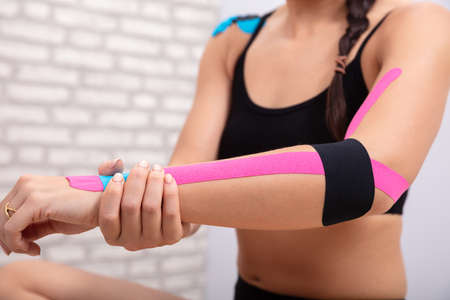 Close-up Of Woman In Sportswear Holding Her Hand With Blue And Black Physio Tape Stock Photo
