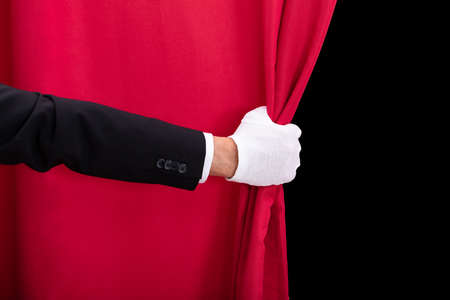 Close-up Of Two Mens Hand Opening Red Curtain