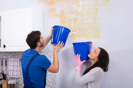 Young Woman And Repairman With Blue Bucket Collecting Water From Damaged Ceiling In Kitchen Фото со стока