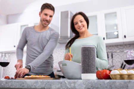 Happy Young Couple Preparing Food In Front Of Wireless Speaker In Kitchen