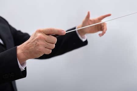 Close-up Of A Music Conductor Hands Holding Baton Against Gray Background Archivio Fotografico