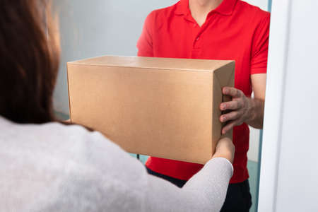 Close-up Of Woman Taking Cardboard Box From Delivery Man