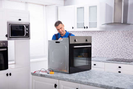Mature Male Technician Repairing Oven On Kitchen Worktop