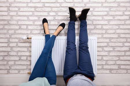 Close-up de una pareja calentando sus pies en el radiador blanco en casa