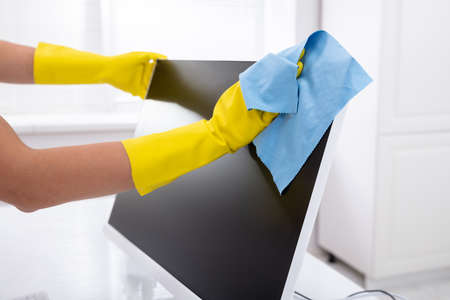 Close-up Of A Person's Hand Cleaning Desktop Screen With Blue Rag In Office Banco de Imagens