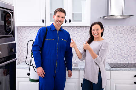 Woman Showing Thumbs Up With Pest Control Worker Standing In Kitchen Zdjęcie Seryjne