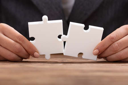 Close-up Of Businesspersons Hand Trying To Join The Two White Jigsaw Puzzle