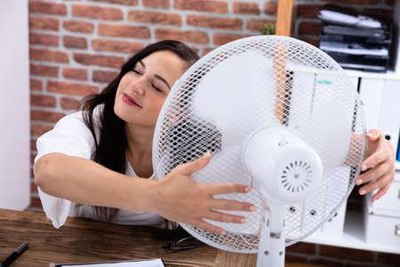 Lächelnde junge Frau genießt Brise mit elektrischem Ventilator im Büro Standard-Bild