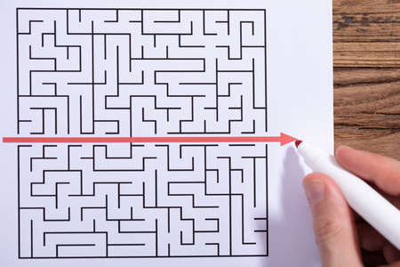 Close-up Of Person's Hand Solving Maze Puzzle With Red Marker Over Wooden Desk Stockfoto - 116953183