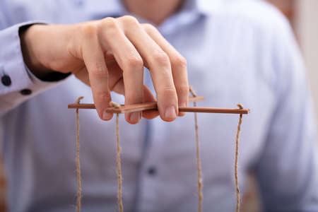 Close-up Of A Businessperson's Hand Manipulating Marionette With A String Stock Photo