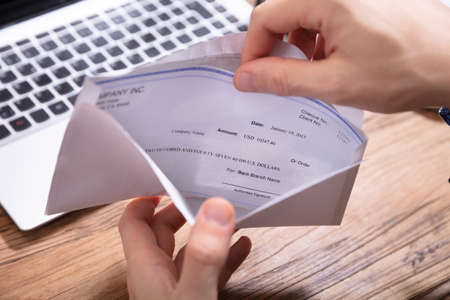Elevated View Of Person's Hand Removing Paycheck From The Envelope Over Wooden Desk