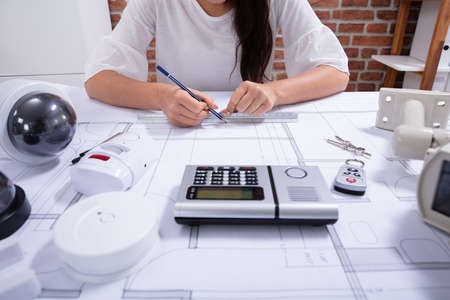 Close-up Of A Female Architect Drawing Blueprint With Pencil On Desk In The Office 版權商用圖片