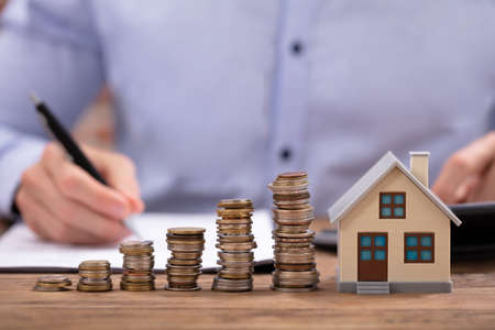 Stacked Coins And House Model On Desk In Front Of Businessman Working On Wooden Desk