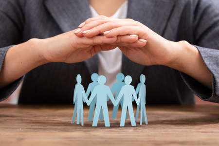 Close-up Of A Businesswoman's Hand Protecting Blue Paper Cut Out Human Figures Forming Circle