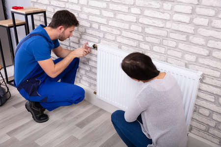 Beautiful Woman Looking At Young Male Plumber In Uniform Installing Radiator With Screwdriver