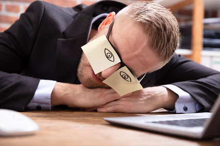 Young Man Covering Her Eyes With Adhesive Notes On Desk In Office
