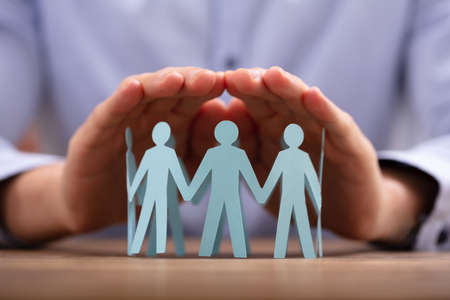 Close-up Of A Person's Hand Protecting Human Figures Forming Circle