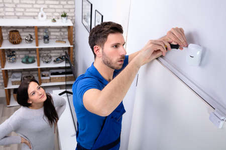 Happy Woman Looking At Electrician Installing Security System Motion Detector On Wall