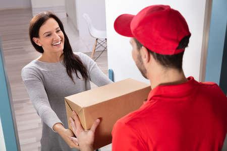 Glückliche junge Frau, die Karton vom Lieferboten akzeptiert