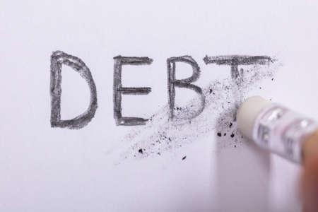 Close-up de borrador de lápiz borrando deuda palabra sobre papel blanco