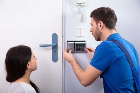 Close-up Of Handyman Installing Security System Near Door Wall While Woman Using Remote Stockfoto