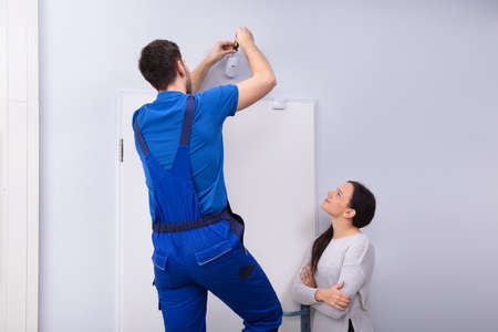 Happy Woman Looking At Electrician Installing Security System Door Sensor On Wall