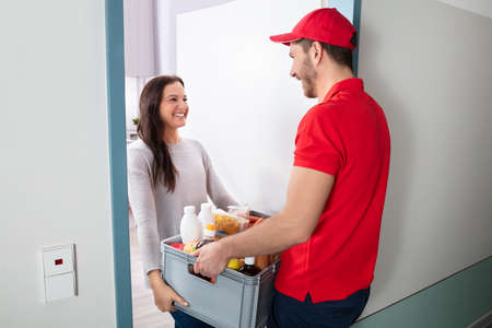 Smiling Young Woman Accepting Full Of Groceries From Delivery Man