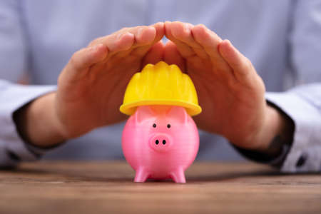 Close-up Of A Person's Hand Protecting Pink Piggy Bank With Yellow Hard Hat