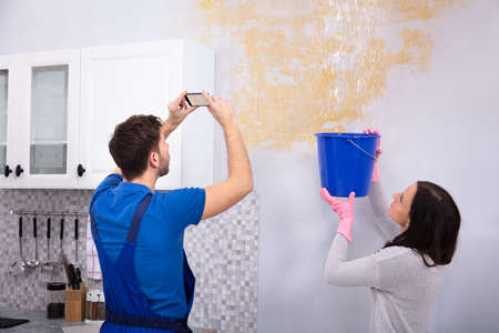 Woman Collecting Water In Blue Bucket From Damaged Ceiling While Repairman Taking Photograph On Mobilephone Stock Photo