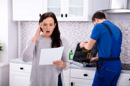 Young Housewife Shocked After Reading Repair Cost Estimate Of Domestic Appliance Banque d'images - 117941530