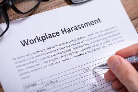 Close-up Of A Mans Hand Filling Workplace Harassment Form