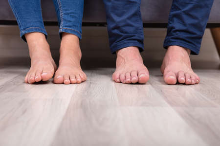 Low Section Of Couples Feet On Floor In Living Room