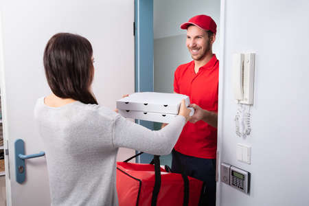 Smiling Woman Receiving Pizza From Delivery Man At Home