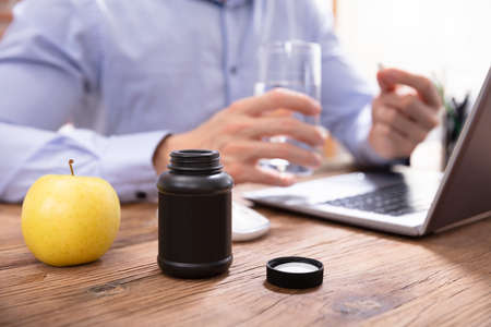 Apple And Pills Bottle In Front Of Businessman Taking Medicines In Office