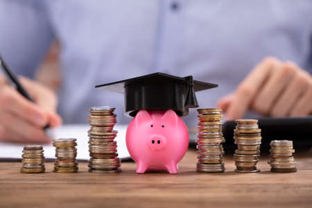 Stacked Coins And Piggy Bank With Graduation Cap In Front Of Businessman Фото со стока - 117941670