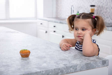 Close-up Of Girl Looking At Cupcake On Kitchen Worktop