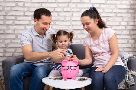 Happy Parents With There Daughter Inserting Coin In Pink Piggy Bank
