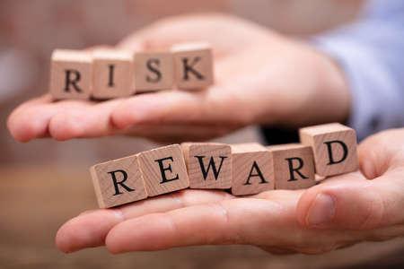Close-up Businessman's Hand Holding Risk And Rewards Blocks Over Wooden Table Reklamní fotografie