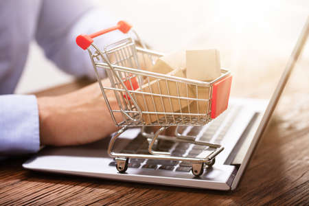Close-up Of Man Using Laptop With Miniature Cardboard Boxes In The Shopping Trolley Archivio Fotografico