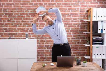 Smiling Young Businessman Standing In Front Of Desk Exercising At Workplace Stock Photo