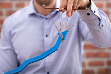 Mid-section Of Person's Hand Manipulating Blue Arrow With Rope