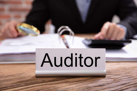 Nameplate With Auditor Title Kept On Desk In Front Of Businessman Examining The Invoices