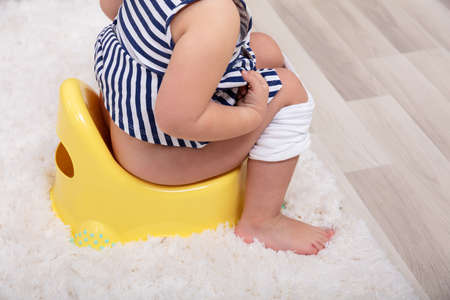 Rear View Of Female Toddler Sitting On A Potty Pot